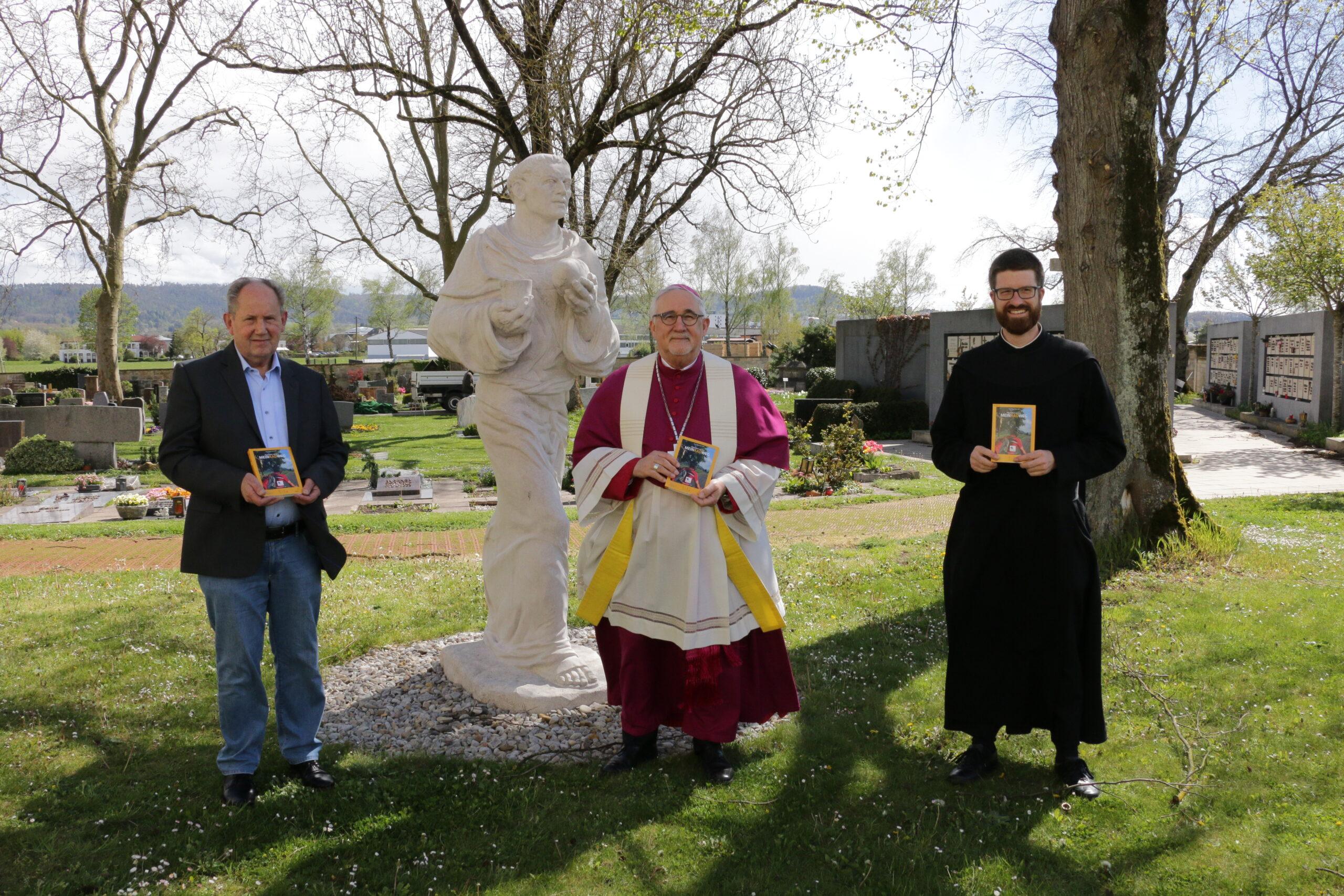 Bischof Gebhard Fürst (Mitte) zusammen mit Verlagsleiter Josef Fink (rechts) und Pater Philipp (links) vor der Statue des heiligen Meinrad. Foto: Gregor Moser, Rottenburg.
